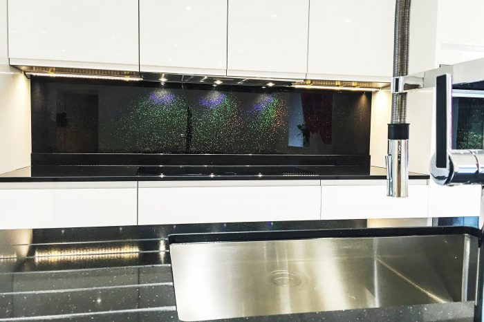 Black coloured glass splashback with rainbow glitter